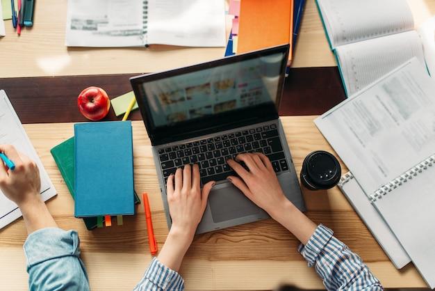 Mãos femininas no teclado do laptop, vista superior, conceito de conhecimento. alunos navegando informações na internet