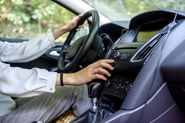 Mãos femininas no volante de um carro. mulher motorista, interior do carro