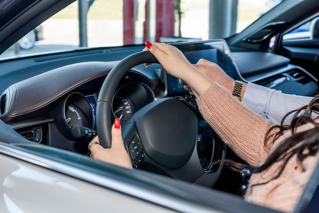 Mãos femininas no volante, interior do carro