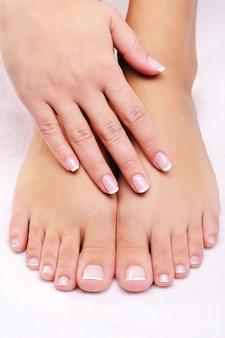 Mãos femininas nos pés bem tratados com pedicure francesa