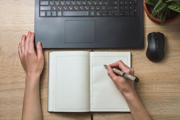 Mãos femininas notebook diário e mouse sem fio. espaço de escritório e ambiente de trabalho. vista do topo