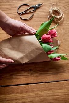 Mãos femininas, organizando o buquê de tulipas cor de rosa na mesa de madeira, florística hobby no local de trabalho, negócios, diy, conceito de presente de primavera, de cima.