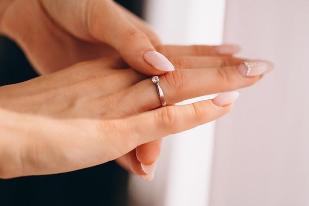Mãos femininas perto com anel de casamento