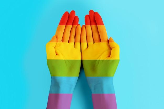 Mãos femininas pintadas nas cores da bandeira lgbt sobre um fundo azul. bandeira da comunidade lgbt, copie o espaço. fundo de tolerância lgbt. conceito de dia do orgulho lgbt