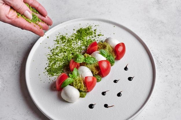 Mãos femininas polvilhadas com migalhas de pão verde para a deliciosa salada italiana caprese com tomates maduros, manjericão fresco e queijo mussarela