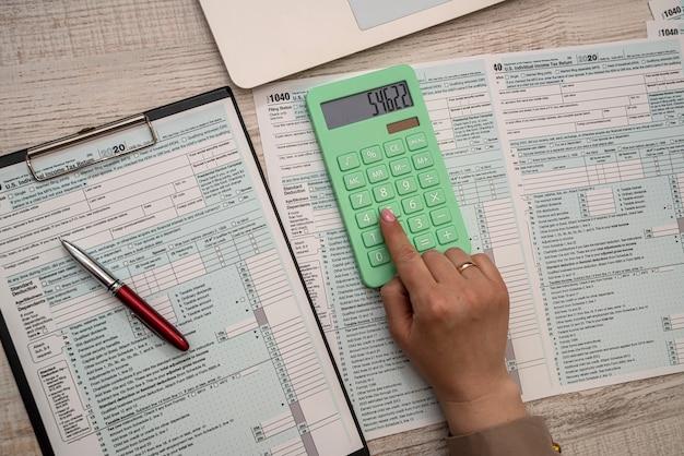 Mãos femininas preenchendo declaração de imposto de renda individual 1040, conceito de papelaria