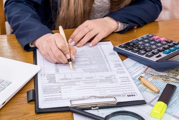 Mãos femininas preenchendo formulário 1040, conceito de tributação