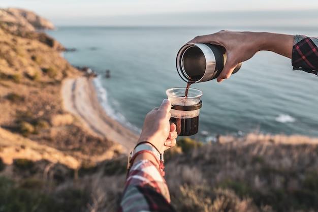 Mãos femininas preparando café em sua xícara com a costa ao fundo. conceito de exploração e aventuras
