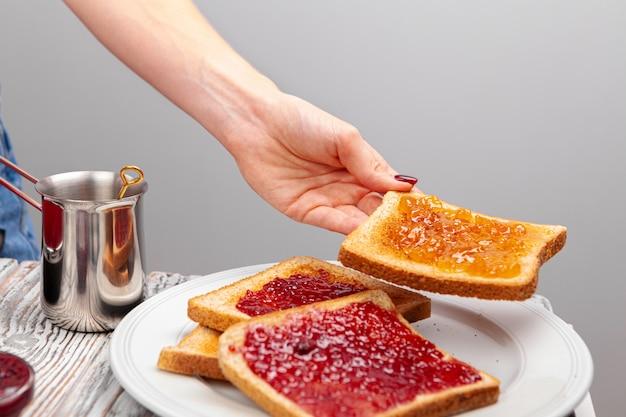 Mãos femininas preparando torradas com geléia de frutas