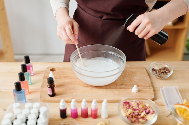 Mãos femininas pulverizando essência aromática na massa líquida de vidro no processo de fabricação de sabonete artesanal