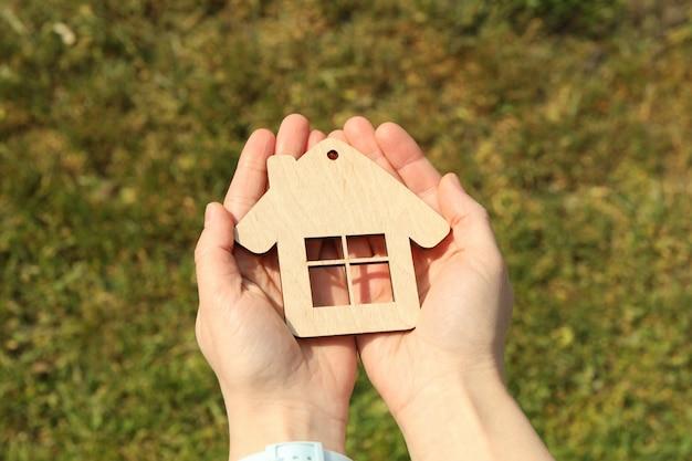 Mãos femininas segura casa de madeira. comprando um imóvel