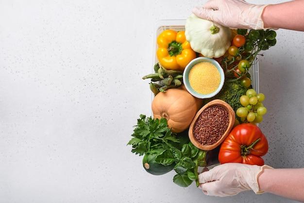 Mãos femininas segura uma caixa de plástico com uma variedade de legumes frescos, frutas, cereais e sementes em fundo de madeira velho. entrega em domicílio segura, cozimento de alimentos e fundo de comida limpa saudável e mock up.