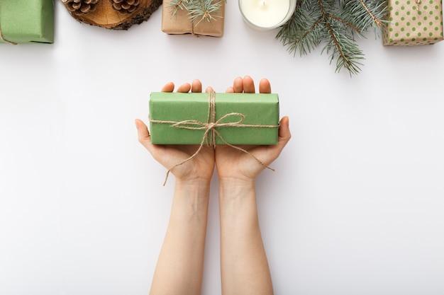 Mãos femininas segura uma caixa de presente de natal na mesa branca. ano novo de natal