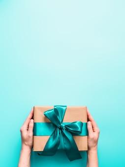 Mãos femininas segura uma caixa de presente grande em fundo azul turquesa, copie o espaço. menina caucasiana com as mãos segurando uma caixa de presente em papel de embrulho artesanal com fita de cetim verde.