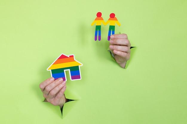 Mãos femininas seguram a bandeira e as pessoas com as cores do arco-íris sobre um fundo verde. conceito lgbt. local para publicidade.