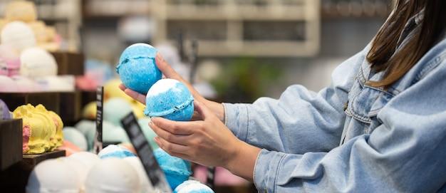 Mãos femininas seguram bombas de banho brilhantes em uma loja de cosméticos. conceito de cuidados com o corpo.