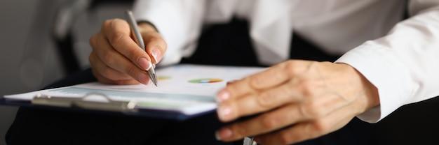 Mãos femininas seguram caneta e klebold com documentos e relatórios de negócios em gráficos