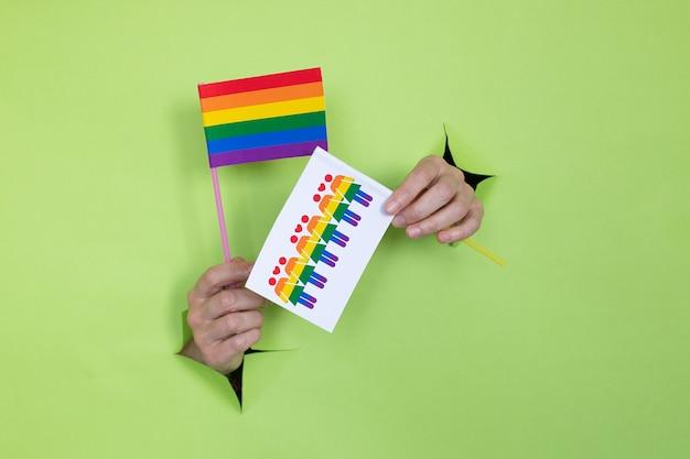Mãos femininas seguram duas bandeiras com as cores do arco-íris sobre um fundo verde. conceito lgbt. local para publicidade.