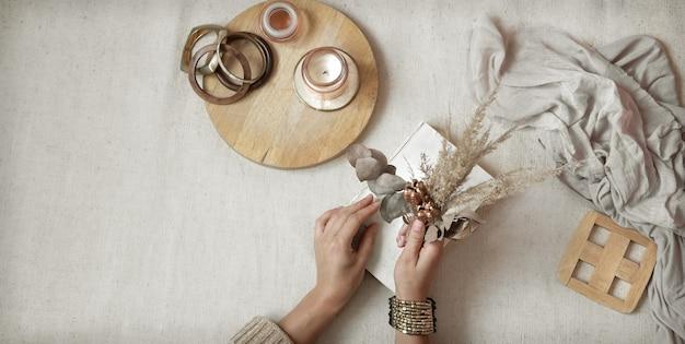 Mãos femininas seguram flores secas com detalhes de decoração em madeira, espaço de cópia e vista superior.