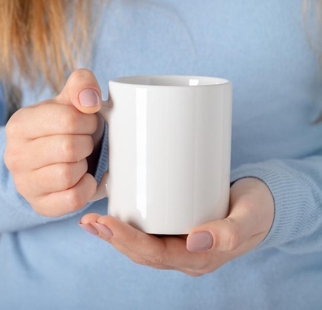 Mãos femininas seguram mock up caneca vazia branca, copo para seu design e logotipo closeup. modelo em branco para mensagem de texto promocional ou conteúdo promocional.