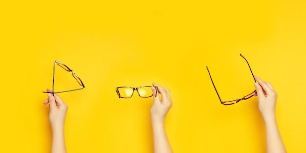 Mãos femininas seguram óculos para visão em um fundo amarelo