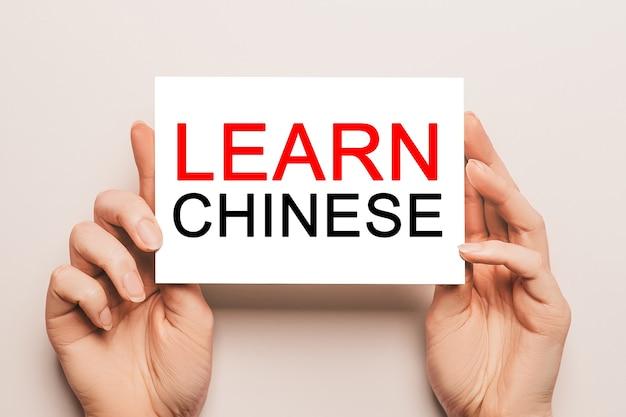 Mãos femininas seguram papel cartão com texto aprenda chinês. educação e conceito de linguagem