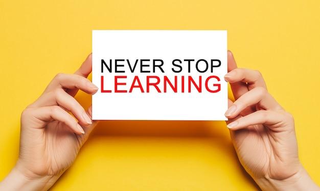 Mãos femininas seguram papel cartão com texto nunca pare de aprender sobre um fundo amarelo. educação e conceito de estudo