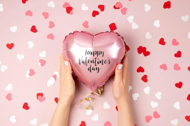 Mãos femininas seguram um balão de folha em forma de coração em fundo rosa pastel. conceito de amor. celebração do feriado. decoração de dia dos namorados ou casamento / despedida de solteira. balão metálico