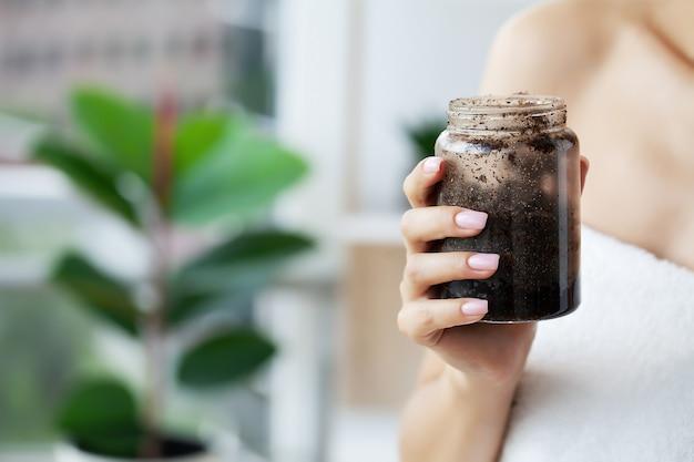 Mãos femininas seguram um frasco de esfoliante de café.