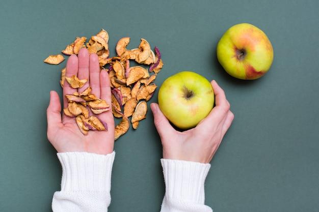 Mãos femininas seguram um punhado de pedaços de maçãs secas e maçãs frescas em um fundo verde