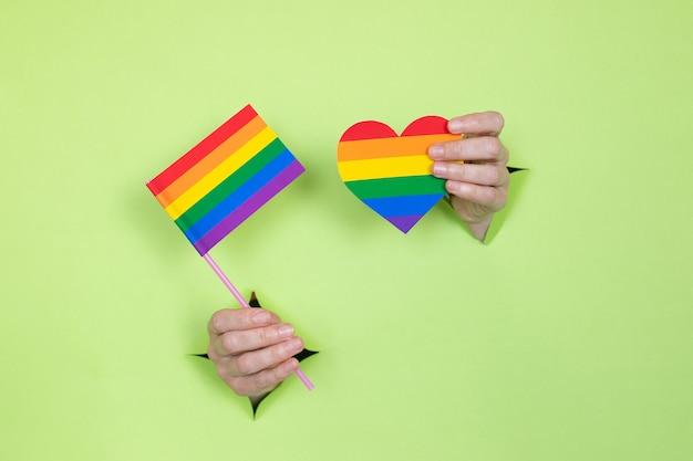 Mãos femininas seguram uma bandeira e um coração com as cores do arco-íris sobre um fundo verde. conceito lgbt. local para publicidade.