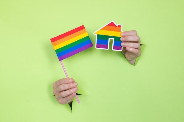 Mãos femininas seguram uma bandeira e uma casa com as cores do arco-íris sobre um fundo verde. conceito lgbt. local para publicidade.