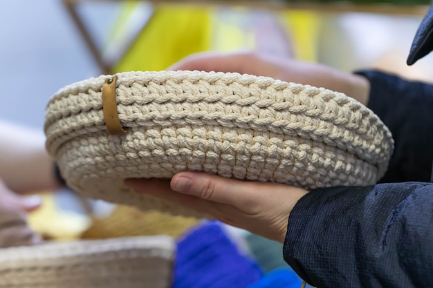 Mãos femininas seguram uma cesta de malha ou vime.