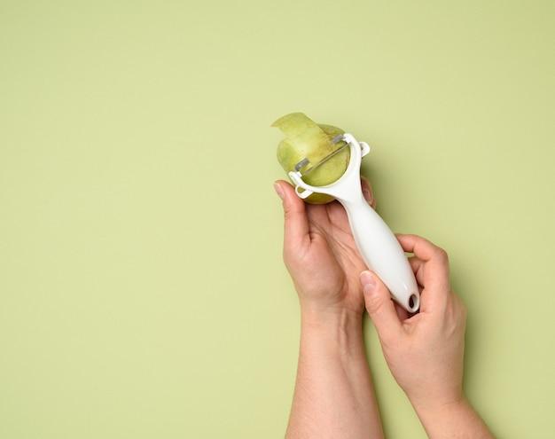 Mãos femininas seguram uma faca de plástico para limpar vegetais e frutas e uma maçã verde sobre um fundo verde, close-up