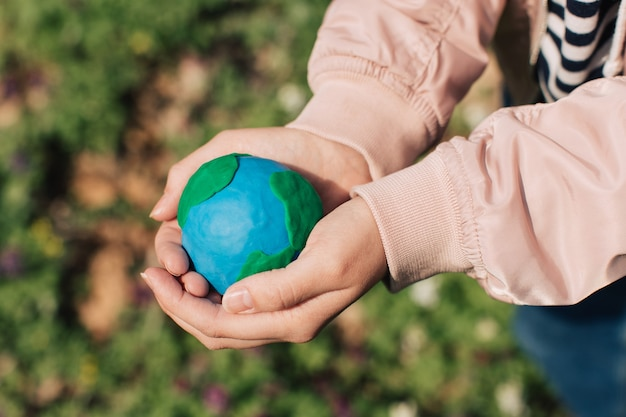 Mãos femininas segurando a terra contra um fundo verde primavera.