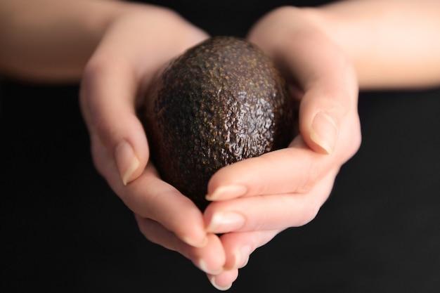 Mãos femininas segurando abacate preto