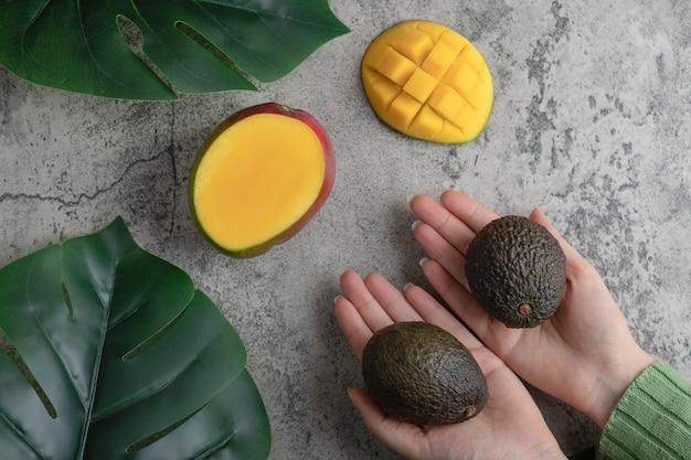 Mãos femininas segurando abacates maduros na superfície de mármore.