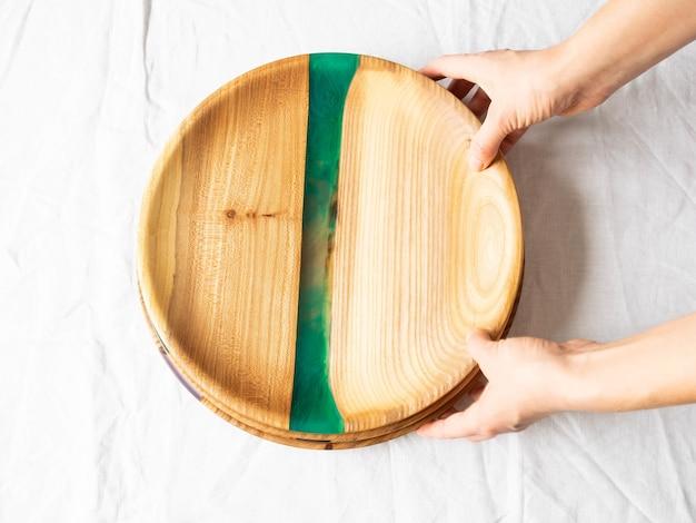 Mãos femininas segurando bandejas redondas de madeira