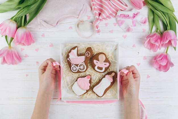 Mãos femininas segurando caixa com biscoitos. uma composição para recém-nascidos