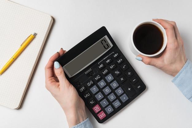 Mãos femininas segurando calculadora e xícara de café em branco. conceito de orçamento.