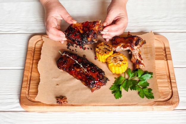 Mãos femininas segurando carne de churrasco acima de uma placa de madeira com carne e milho