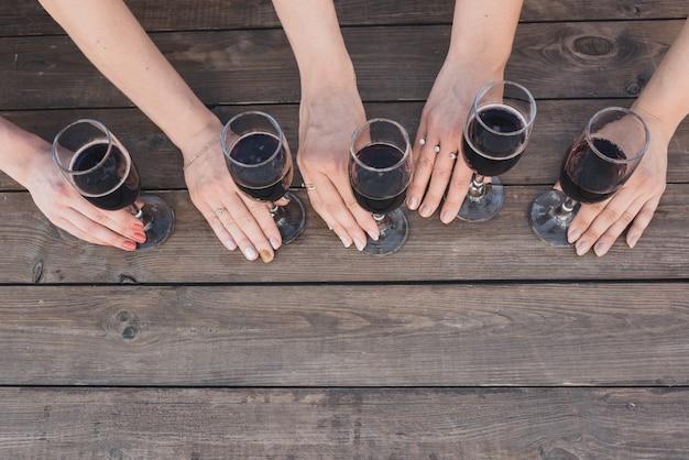Mãos femininas segurando copos com vinho tinto em tábuas de madeira