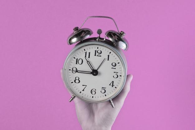 Mãos femininas segurando despertador retrô rosa