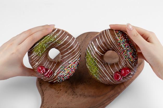Mãos femininas segurando dois donuts de chocolate deliciosos em uma tábua de madeira.