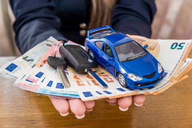 Mãos femininas segurando euro, carro de brinquedo e chaves