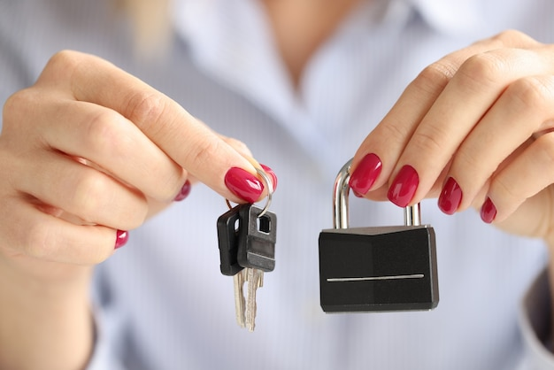 Mãos femininas segurando fechadura de ferro e closeup de chaves. conceito de segurança doméstica