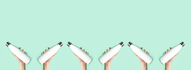 Mãos femininas segurando garrafas térmicas de aço eco reutilizáveis brancas