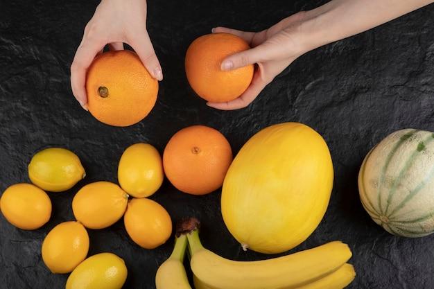 Mãos femininas segurando laranjas frescas maduras na mesa preta.