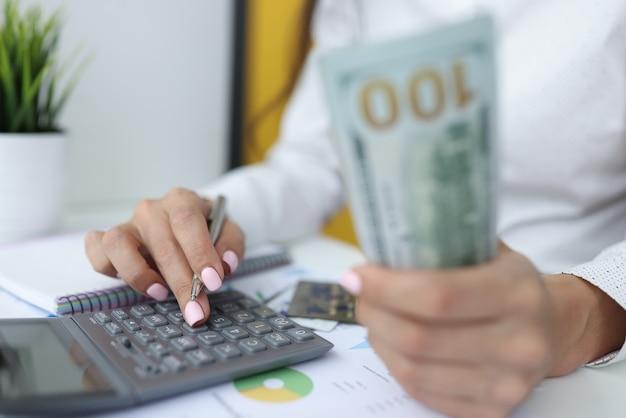 Mãos femininas segurando notas de cem dólares