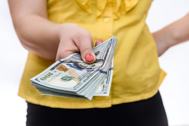 Mãos femininas segurando notas de dólar em leque